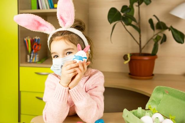 Menina nas orelhas de lebre faz um coelhinho da páscoa em máscara médica de um ovo e plasticina.