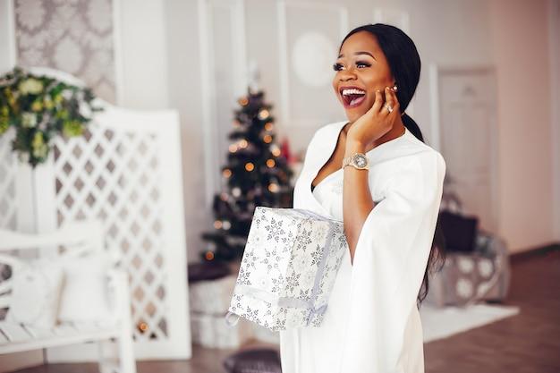 Menina negra elegante na sala de natal decorada