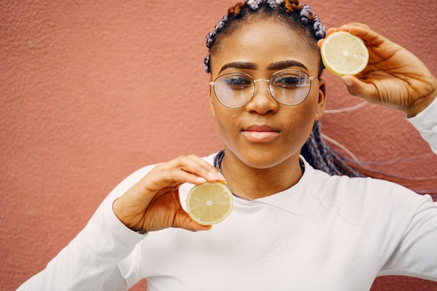 Menina negra em pé em uma parede com um limão