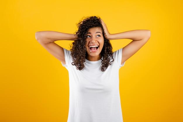 Menina negra estressada, cobrindo as orelhas dela isoladas sobre amarelo