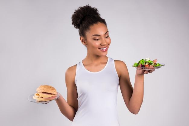 Menina negra segurando cheeseburger e salada isolado