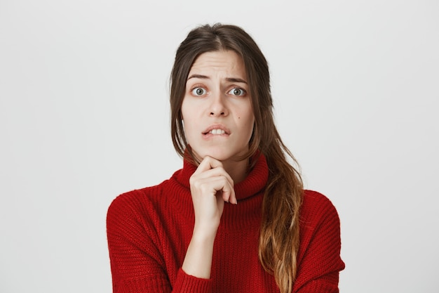 Menina nervosa tem dúvidas, mordendo o lábio preocupado