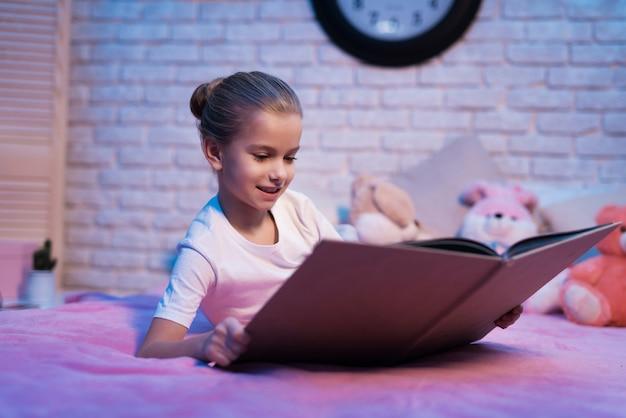 Menina, neta está lendo o livro à noite em casa