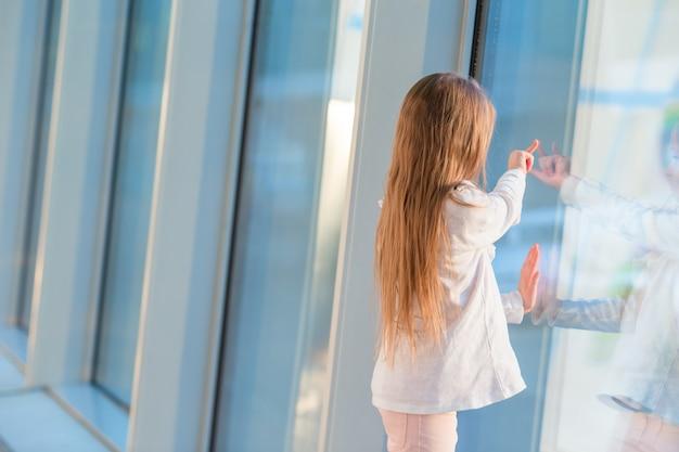 Menina no aeroporto perto da grande janela enquanto aguarda o embarque