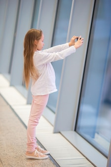 Menina no aeroporto perto da grande janela enquanto espera pelo embarque