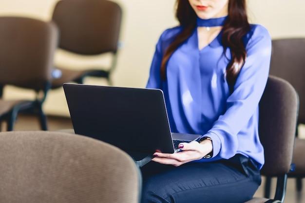 Menina no auditório trabalha com laptop
