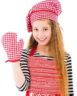 Menina no avental vermelho e luva de cozimento