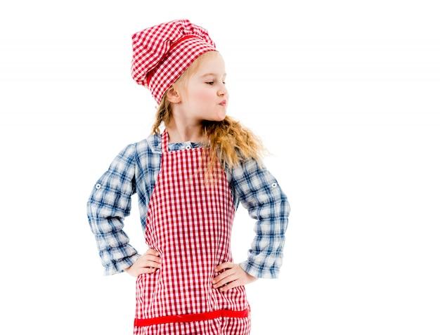 Menina no avental xadrez vermelho em pé em pose akimbo