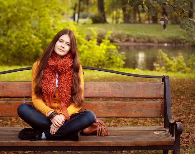 Menina no banco no parque outono