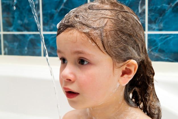 Menina no banheiro lavando o cabelo dela. o símbolo da educação em pureza e higiene.