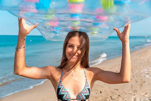 Menina no beira-mar que veste biking que guarda o colchão inflável. retrato de uma jovem mulher sozinha na praia, olhando para a câmera em um dia ensolarado. foto bonita do verão de viagens