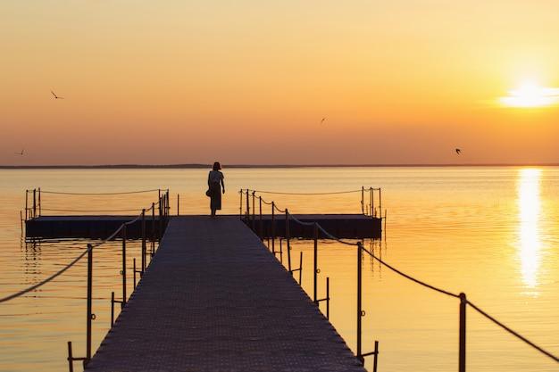 Menina no cais do pontão ao pôr do sol