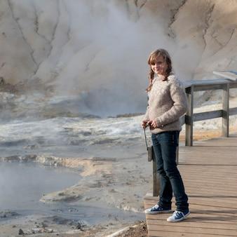 Menina no calçadão ao lado de respiradouros de geyser geotérmica