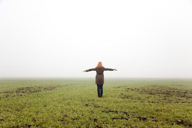 Menina no campo da mola no tempo de névoa.