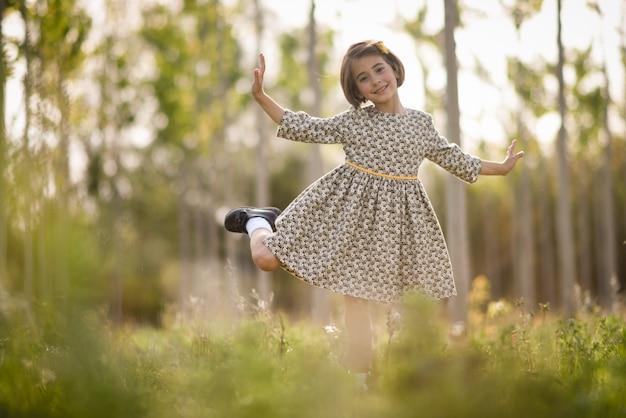 Menina no campo da natureza que desgasta o vestido bonito