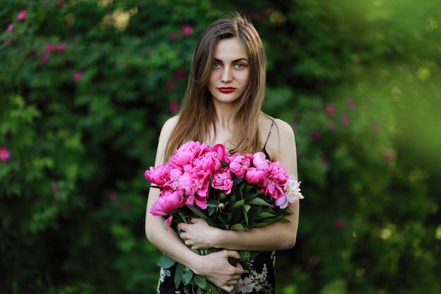 Menina no campo de flores. retrato de uma menina com flores cor de rosa