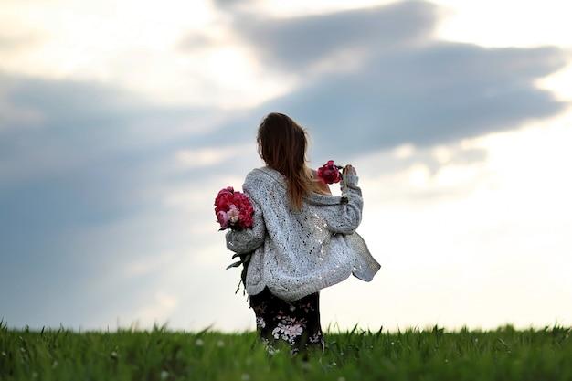 Menina no campo de flores. uma menina com peônia anda no campo