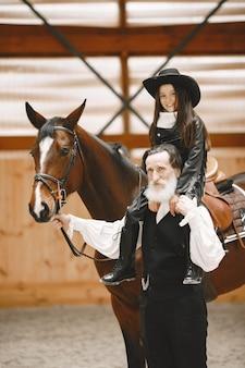 Menina no capacete aprendendo a andar a cavalo. o instrutor ensina a garotinha.