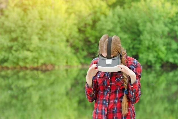 Menina no capacete da realidade virtual no contexto da natureza. olhando para baixo
