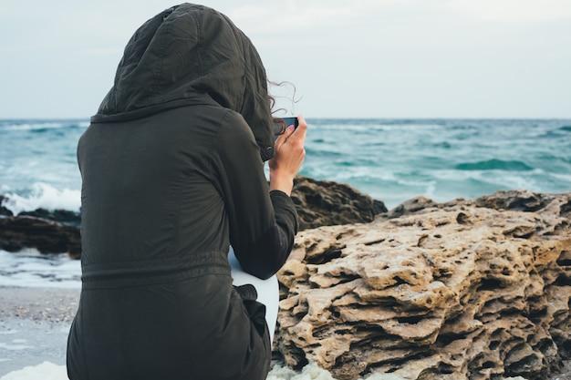 Menina no capuz verde sentado na praia fotografando o mar e as pedras rochosas no telefone