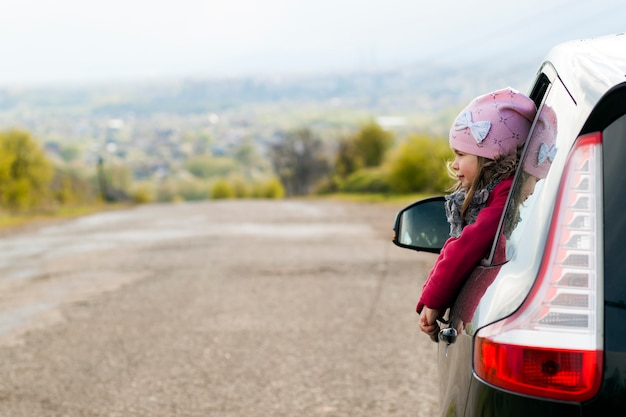 Menina no carro olhando pela janela.