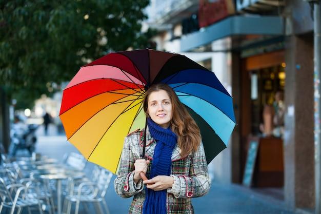 Menina no casaco de outono com guarda-chuva