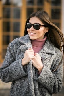 Menina no casaco de pé na rua