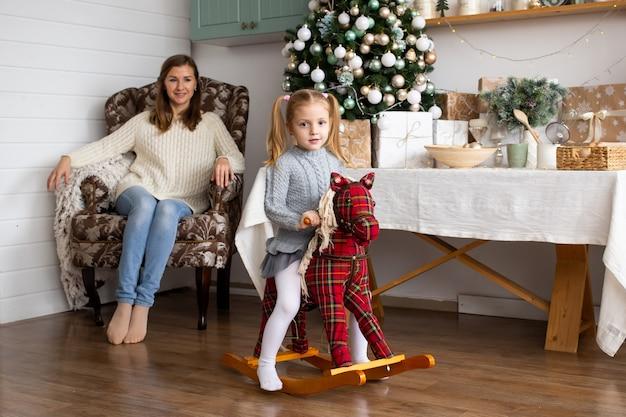 Menina no cavalo do brinquedo e sua mãe na cozinha do natal em casa.