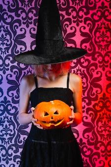 Menina no chapéu de bruxa segurando abóbora