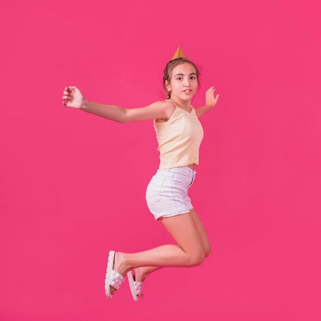 Menina no chapéu de festa pulando no pano de fundo rosa