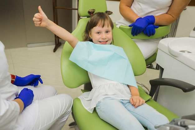 Menina no dentista sorrindo e dando polegares para cima
