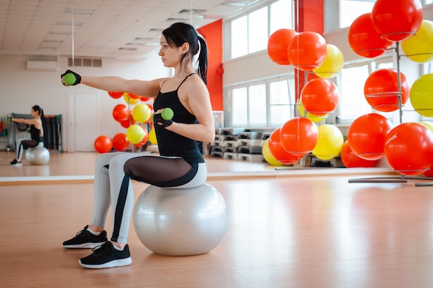 Menina no ginásio fazendo exercícios de fitness.