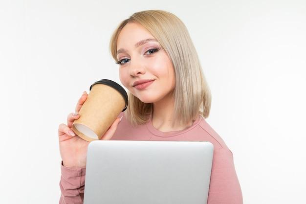 Menina no intervalo do café com uma xícara de café e um laptop nas mãos dela sobre um fundo branco