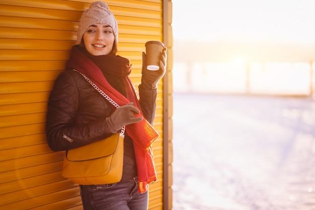 Menina no inverno segurando café em luvas