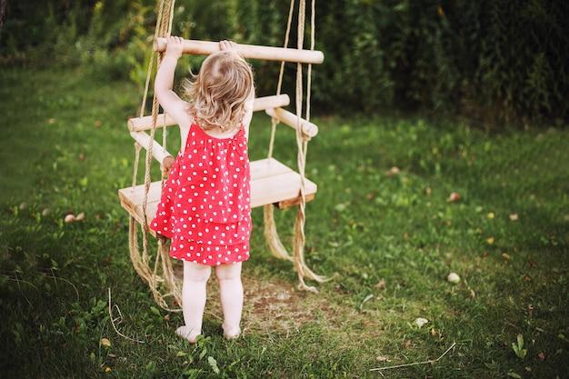 Menina no jardim brincando com balanços