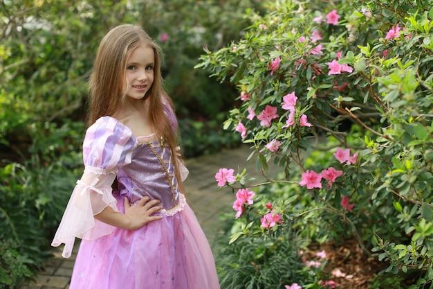 Menina no jardim com azaléias em vestido de princesa