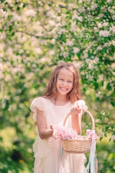 Menina no jardim de maçã florescendo no lindo dia de primavera