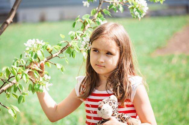 Menina no jardim na primavera, galho de árvore de maçã, primavera, beleza, vestido, infância, criança