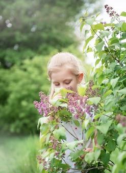 Menina no jardim perto dos arbustos de lilases