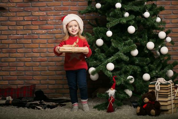 Menina no natal com caixa de presente pela árvore de natal