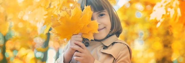 Menina no parque com folhas de outono.