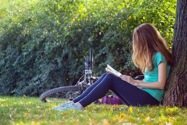 Menina no parque fica sob uma árvore e lê um livro. ao lado dela está uma bicicleta e uma mochila