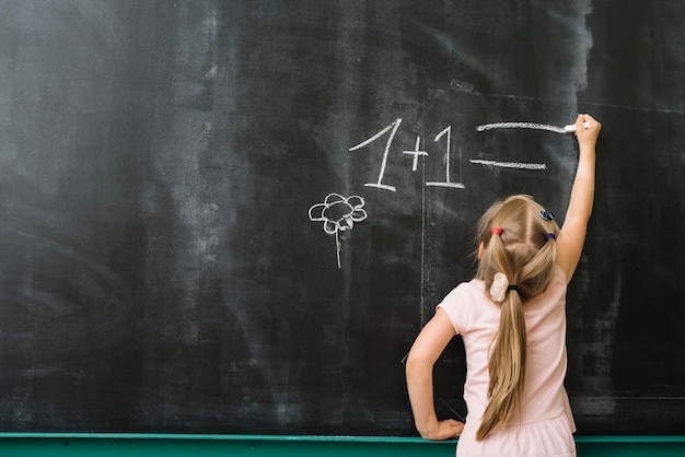 Menina no quadro-negro na aula de matemática