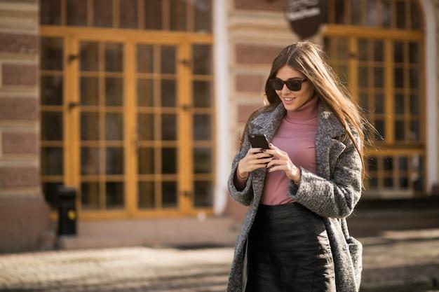 Menina no revestimento com o telefone em pé na rua