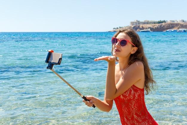 Menina no roupa de banho com um telefone esperto na praia. menina tomando selfie diversão na praia