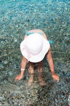 Menina no roupa de banho e chapéu branco no mar. férias de verão no mar egeu, ilha de kos, grécia