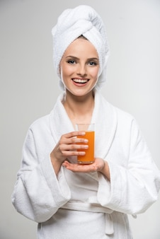 Menina no roupão que bebe o suco de laranja.