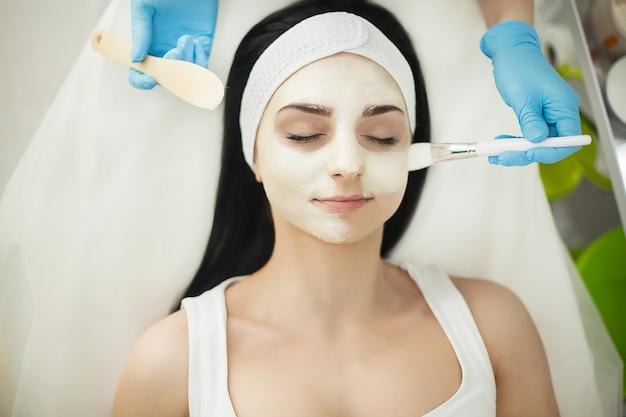 Menina no salão de spa. esteticista aplicando pó cosmético branco