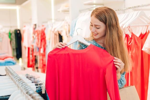 Menina no shopping verificando a blusa vermelha
