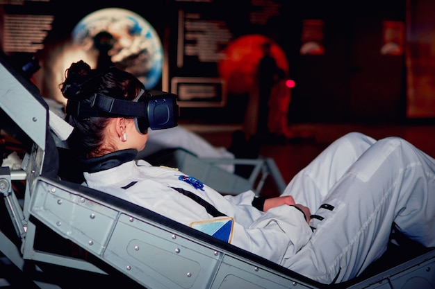 Menina no simulador espacial para sastronauts ou cosmonautas com uma realidade virtual glasse